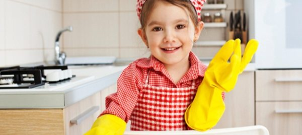 Little Girl holding sponge and smiling in the kitchen